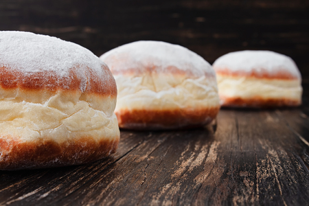 Freshly made doughnuts filled with jam and covered in powdered sugar on a rustic wooden table