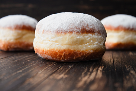 Freshly made doughnuts filled with jam and covered in powdered sugar on a rustic wooden table 스톡 콘텐츠 - 119547572