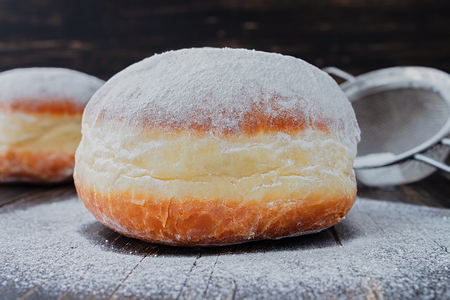 Freshly made doughnuts, heavily covered in powdered sugar on a an old wooden table Stock Photo