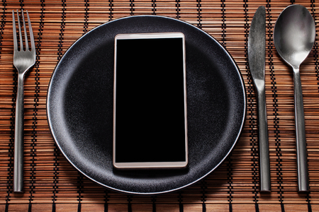 Smartphone served on a black plate with cutlery on the side, concept of social media addiction