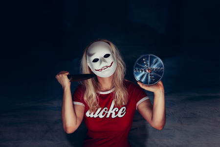 Blonde woman under white mask with spooky bloody smile, holding knife and blade in self defense, horror concept