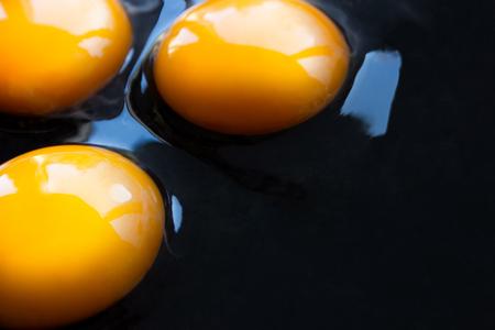 Three fresh raw chicken egg yolks spilled on a dark pan Stok Fotoğraf