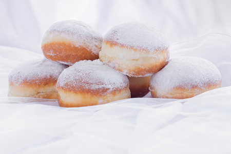 Jelly filled doughnuts with powdered sugar on a bed with white sheets