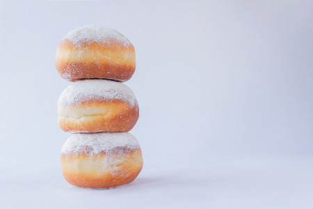 Three fresh doughnuts stacked on each other on white background