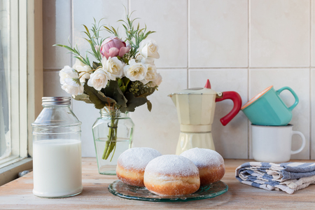 Three fresh doughnuts on a glass plate with coffee cups, moka pot, flowers and milk bottle in background, by the window