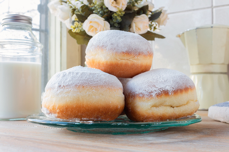 Three fresh doughnuts on a glass plate with moka pot, flowers and milk bottle in background Stock Photo