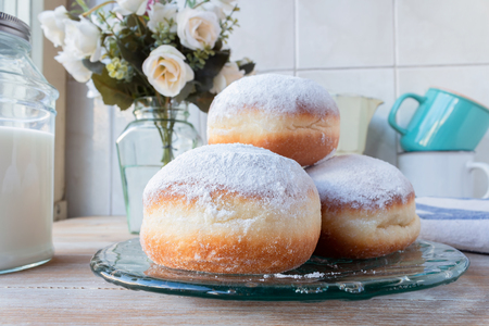 Three fresh doughnuts on a glass plate with coffee cups, flowers and milk bottle in background 스톡 콘텐츠 - 119547641