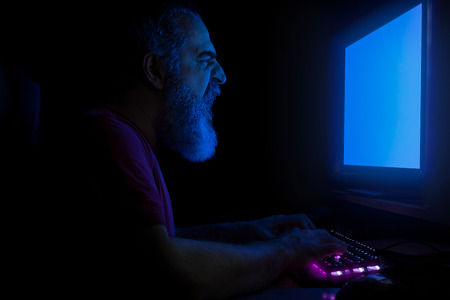 Bearded man screaming in front of computer monitor, hands on a keyboard, working, frustrated, illuminated with blue light from monitor 스톡 콘텐츠 - 119547687