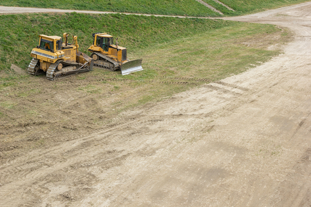 Two bulldozers parked on a patch of grass by the dirt road on a  construction site