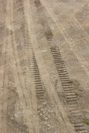 Tire tracks on a brown dirt road, textured imprints in different directions