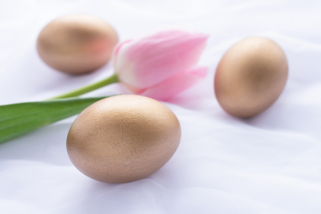 Three golden Easter eggs and pink tulip laying on white fresh linen 스톡 콘텐츠 - 119547753