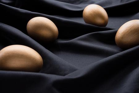 Elegant golden Easter eggs on a silky black background 스톡 콘텐츠 - 119547758