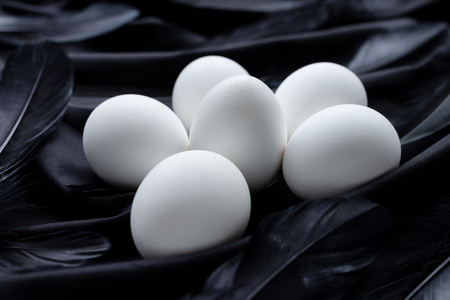 Group of white Easter eggs and black feathers on a black silky background