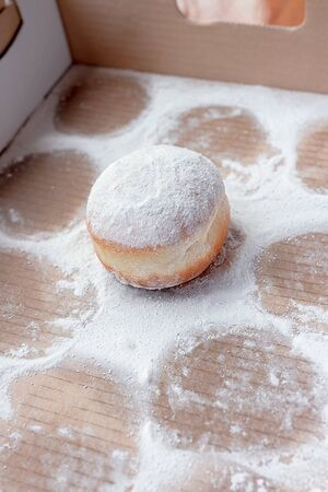 Last doughnut left in the box, surrounded with imprints in powdered sugar of already eaten doughnuts 스톡 콘텐츠