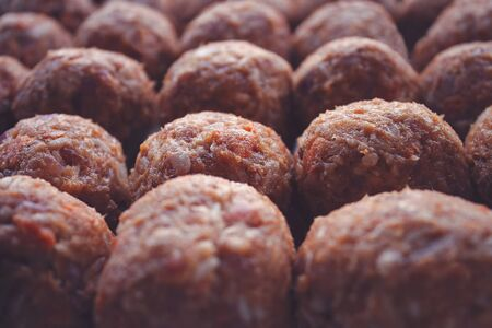 Many rows of freshly made meat balls ready for cooking