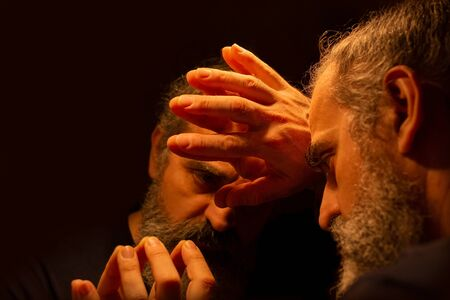 Reflection of bearded man in a dark, holding his head with his hands with painful expression on his face