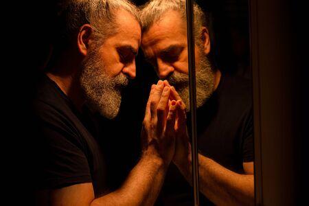 Reflexión del hombre barbudo en la oscuridad, sosteniendo su cabeza con las manos con expresión dolorosa en su rostro Foto de archivo