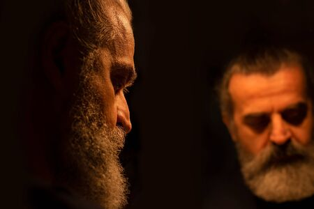 Spiegelbild eines bärtigen Mannes im Dunkeln, mit schmerzhaftem Gesichtsausdruck, allein, traurig und deprimiert Standard-Bild