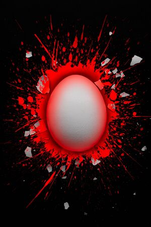 White egg in a puddle of red color with pieces of broken egg shell around it, Easter concept