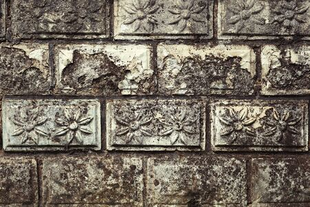 Stone wall with flower relief on each stone brick, old and weathered