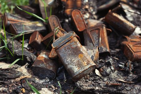 Burnt old rusty cans thrown away in the forest
