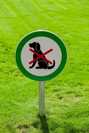Freshly cut green grass with round sign forbidding dogs, no dogs allowed 스톡 콘텐츠