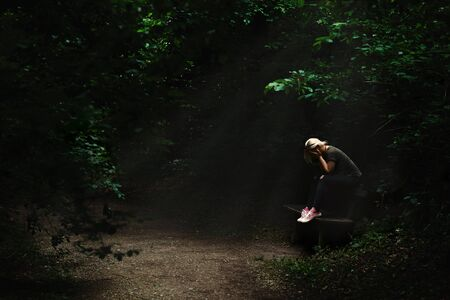 Lonely and sad blonde woman sitting on a bench in a light spot in the middle of dark forest path, surrounded with green trees