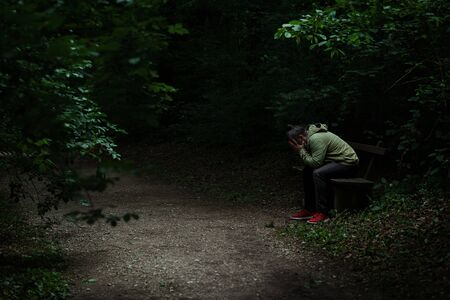 Man sitting on a bench in light spot on forest path, surrounded with darkness, covering his face with his hands, alone, sad and depressed
