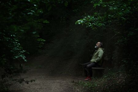 Man sitting on a bench in light spot on forest path, surrounded with darkness, looking up full of hope, rays of light coming thru the tree tops 스톡 콘텐츠