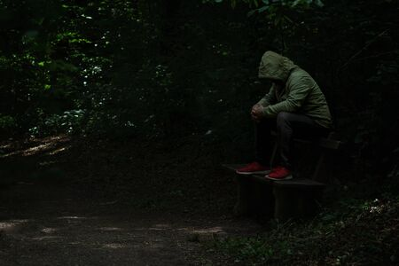 Man sitting on a bench in light spot on forest path, surrounded with darkness, green hoodie covering his face, alone, sad and depressed