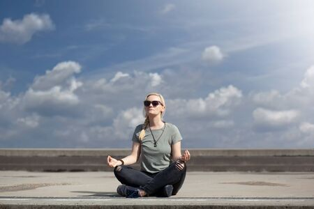 Blonde urban woman in dark jeans and sneakers, sitting in the middle of pavement, taking a break and meditating, with beautiful blue sky with white clouds behind her, on a bright sunny day