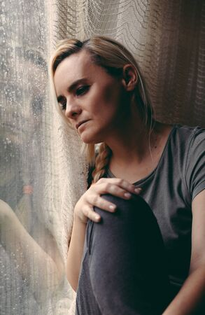Blonde woman sitting by the rainy window, looking absently out, sad, lonely and depressed