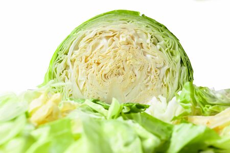 Cabbage head cut in half, isolated on a white background, with shredded cabbage leaves in foreground 스톡 콘텐츠
