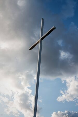 Large metal cross with blue sky and white clouds in the background