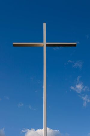 Large metal cross against blue sky background with parts of white clouds