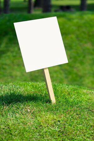 Cartello bianco vuoto su una piccola collina con erba verde appena tagliata e prato sullo sfondo