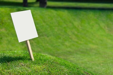 Empty white sign board on a small hill with freshly cut green grass and meadow in the background