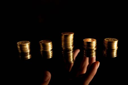 Stacks of coins on the dark background and hand reaching underneath stealing them Banco de Imagens