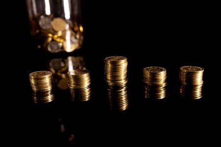 Stacks of coins on the black background with jar filled with coins behind them