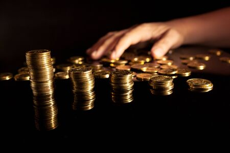 Stack of coins with pile of coins in the background and hand grabbing them