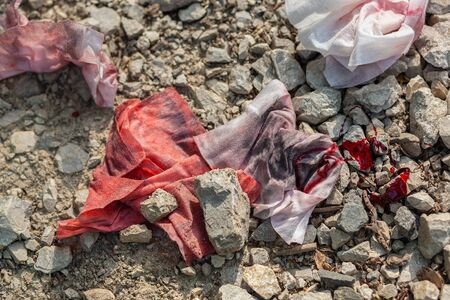 Dirty, old, bloody rags thrown away on the abandoned gravel road