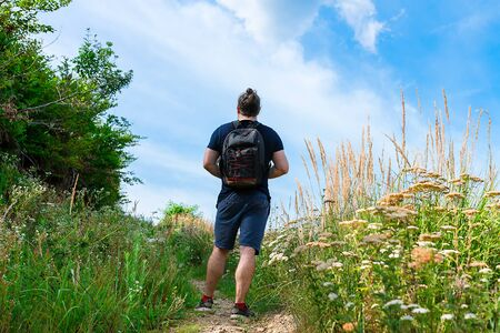 Hiker in blue shorts standing on the mountain trail, almost at the top, with backpack on his back, surrounded with green grass and field flowers, on a sunny day with bright blue sky