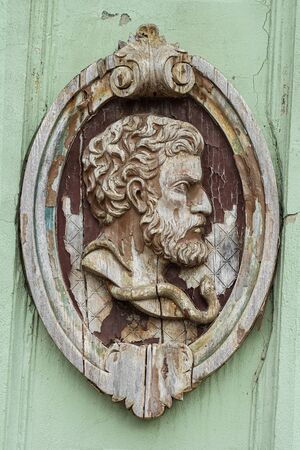 Wooden sculpture of male head in elliptical decorative frame, old and weathered, decorative relief on an old building