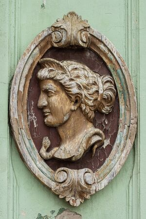 Wooden sculpture of female head in elliptical decorative frame, old and weathered, decorative relief on an old building