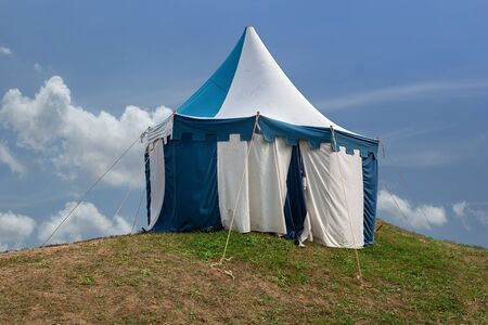 Blue and white medieval tent standing on the hill top with blue sky and white clouds in the background