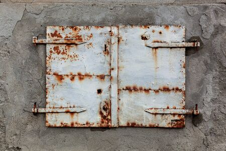 Old, rusty and weathered metal window coverings, closed shut on building exterior