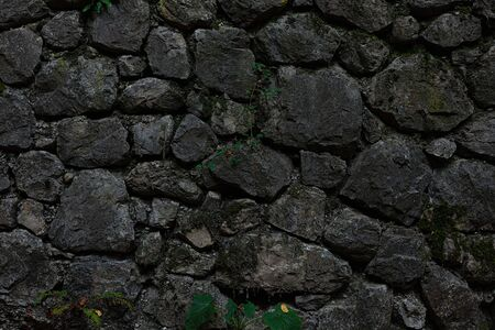 Dark grey stone wall, mixed small and big stones 스톡 콘텐츠