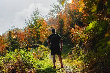 Man standing on a hiking trail with backpack on his back, surrounded with trees in all the autumn colors