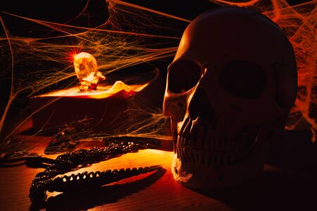 Human skull in the orange candle light, surrounded with cobwebs, on the table with old book, gemstone and pendant Stock Photo