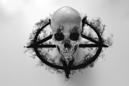 White human skull on top of black pentagram on white background with black smoke 스톡 콘텐츠